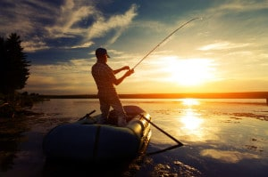 47383037 - fisherman with rod in the boat on the calm pond at sunset