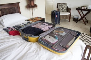 27226035 - open suitcase with holiday clothing being packed